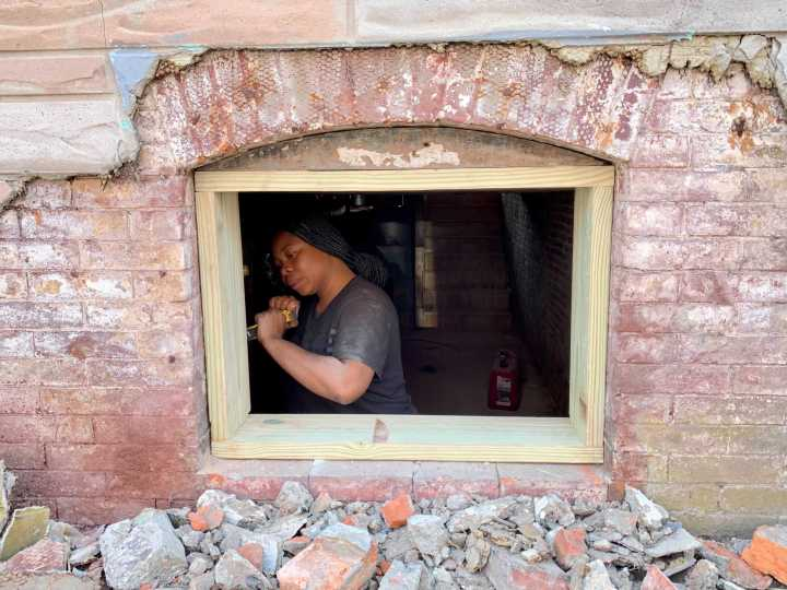 Bryanna Vellines, 28, installs a window frame in an old Baltimore row house. Amy Scott/Marketplace